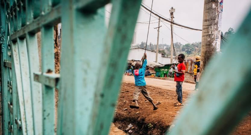 Dos niños juegan con una especie de tirolina ante una valla
